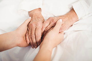 Lay Ministry Nurse Holding Elderly Hands